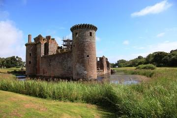 Castello Scozzese in parte in rovina, di forma triangolare, con fossato e torre.