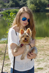 Happy young girl owner with yorkshire terrier dog