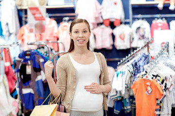 happy pregnant woman shopping at clothing store