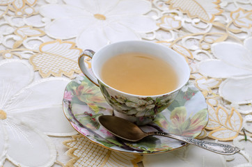 green tea in a vintage decorative cup with metal spoon and fitting plate on a white ornamental table cloth