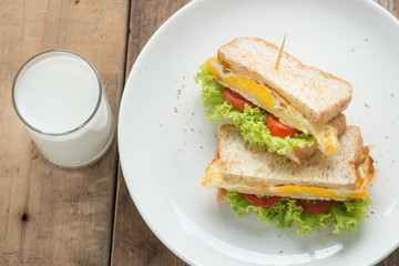 Sandwich fried egg with cheese and milk.