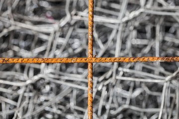 Cross of rusty steel on wire background for abstract background