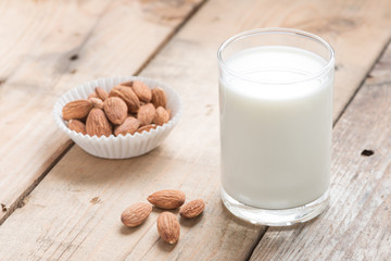 Almond milk with almond on a wood table.