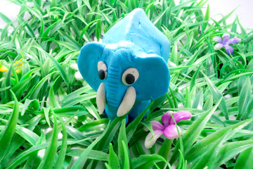 Blue Plasticine elephant standing on plastic grass