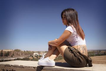 Chica joven española con tatuaje. Mujer con tatuaje posando.