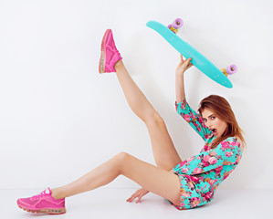 Fashion hipster girl in colorful dress with skateboard having