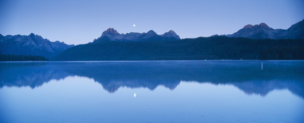 Moonset at sunrise over Redfish Lake and Sawtooth Mountains, Idaho