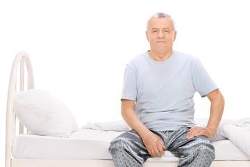Senior man in pajamas sitting on a bed
