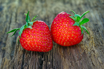Two ripe strawberries on a wooden background