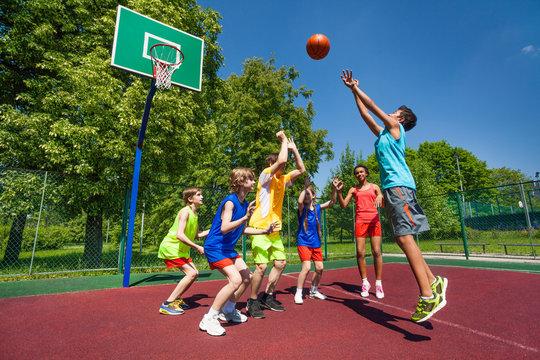 Teenagers playing basketball game together