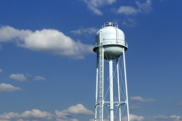A water tower with a lightly cloudy sky in the background.