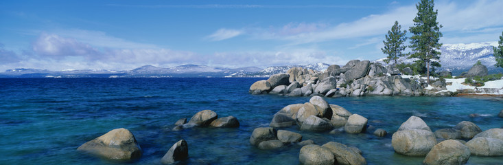 Wall Mural - This is Lake Tahoe after a winter snow storm. There is a full moon over the lake and snow on the sandy shore.