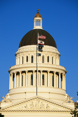 This is the State Capitol dome at sunset. It has several flags waving in the wind on a flagpole in front of it, the top one is the American flag.