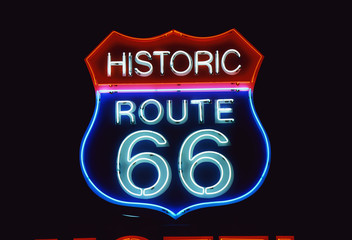Fotobehang Route 66 This is a road sign that says Historic Route 66. It is a neon sign in red, white and blue against a black night sky.