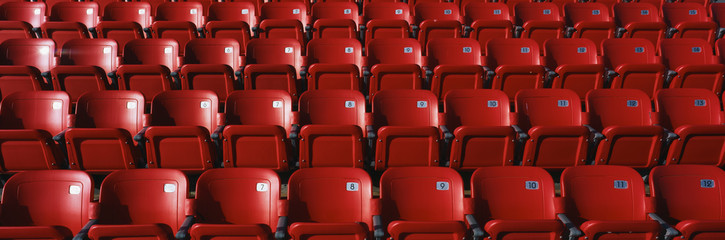 These are bright red outdoor stadium seats with seats that fold up. They are located at a baseball stadium.