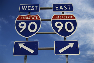 This is a road sign on the New York State Freeway. It points out the direction for Route 90 to go east or west. The signs are blue, red and white against a blue sky.