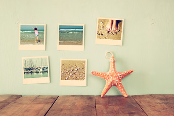 instant photos hang over wooden textured background next to decorative starfish