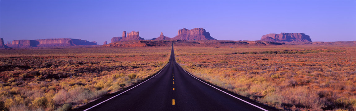 This is Route 163 that runs through the Navajo Indian Reservation. The road runs up the middle and gets smaller into infinity. The red rocks of Monument Valley are in the background. The scrub plants of the desert are on either side of the road.