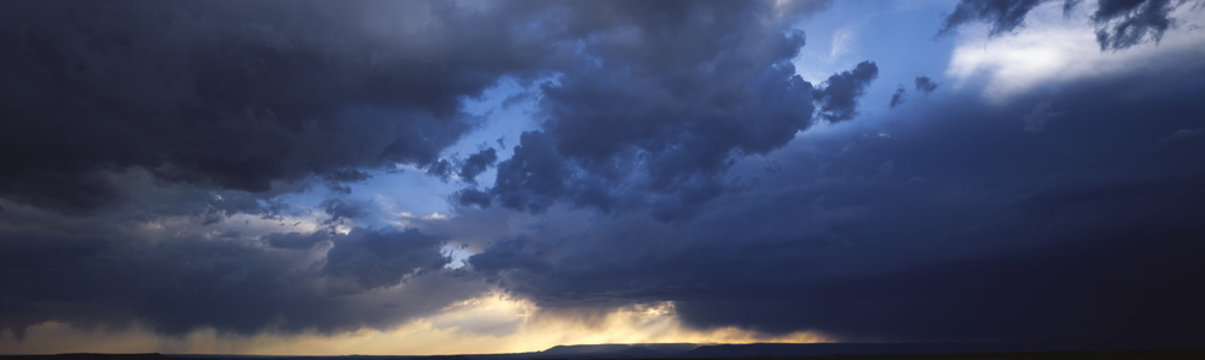 Dark clouds over the mountains of the Southwest. Sunlight on horizon starting to clear in western sky.