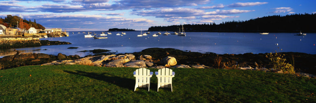 This is an image of two white lawn chairs facing toward the nearby harbor. There are fishing boats moored in the harbor in this small lobster village. The chairs are surrounded by green grass and the harbor has clear blue water. The sky is blue with white clouds.