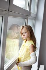 a little girl with a broken arm , window