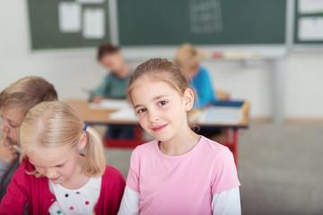 süßes mädchen in der grundschule schaut lächelnd in die kamera