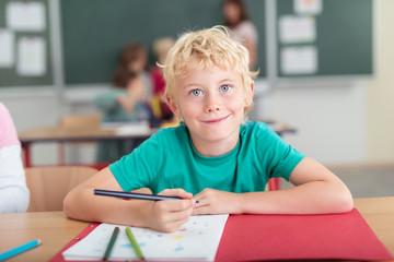 lächelnder kleiner junge in der grundschule