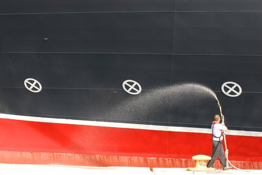 Docker with a water hose near huge cruise ship