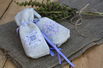 Sachet with ukrainian embroidery, sheaf of wheat and dried herbs on wooden background
