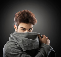 Man in gray cowl neck hoodie hiding his face