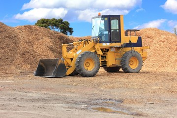 Front end loader with piles of chip bark ready to be loaded and moved