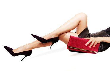 Beautiful legs woman with black high heels,holding a red handbag. laying down on the floor isolated on white.