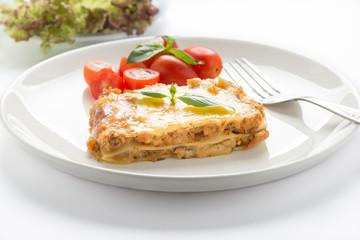 fresh lasagna with basil on white background