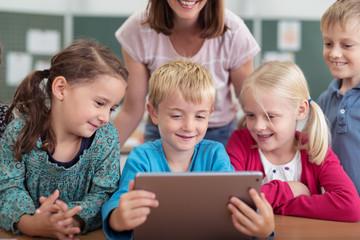 kinder in der grundschule schauen gemeinsam auf ein tablet