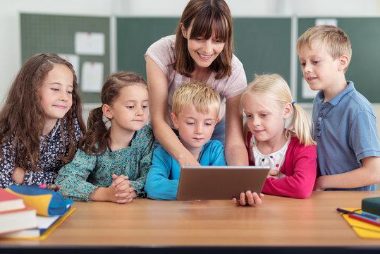 lehrerin zeigt kleinen kinder etwas am tablet