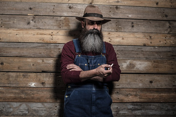 Smoking vintage worker man with long gray beard in jeans dungare