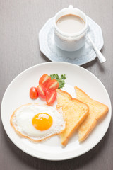 breakfast with fried eggs and toasts on wooden table