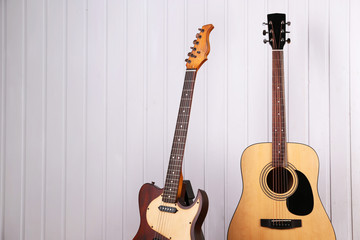 Guitars on white wooden wall background