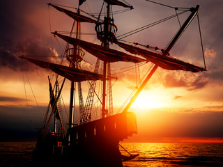 Fototapeten Schiff Old ancient pirate ship on peaceful ocean at sunset.