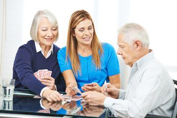 Familie mit Senioren spielt Karten
