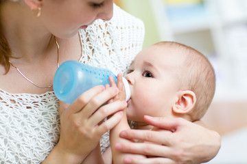 Young mother at home feeding baby with milk bottle, feeling