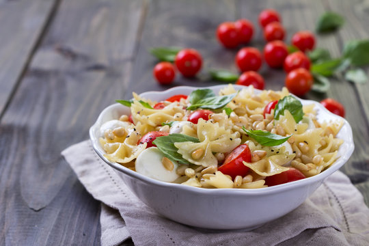 Pasta salad with tomato, mozzarella, pine nuts and basil in a white ceramic bowl on a wooden table