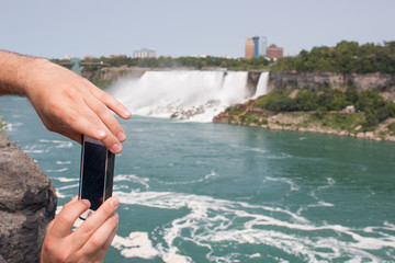 Tourist is making a picture of the Niagra Falls with his Smart Phone