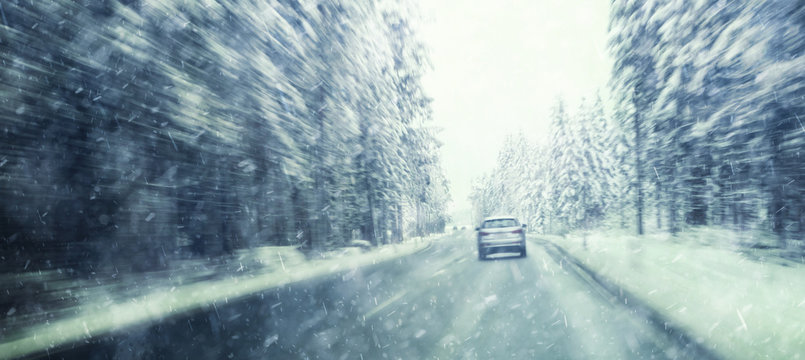 Danger and fast speed driving at the heavy snowy and icy road. Motion blur visualizies the speed and dynamics.