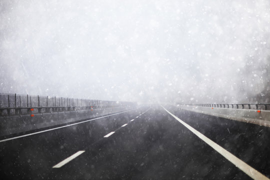 Heavy snowy and foggy winter highway road background with no cars. Danger heavy snowfall empty road background with copyspace. Conceptual photo.