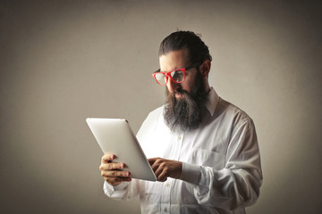 Long-bearded man using a tablet