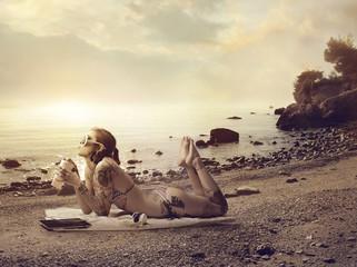 Tattooed girl lying at the beach