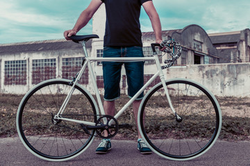 Young man with a fixie bike. Decadent industrial setting
