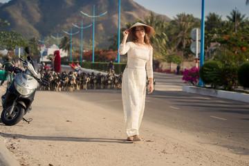 blonde girl in Vietnamese dress walks against goats flock