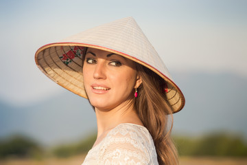 face of girl in Vietnamese hat against blurred background